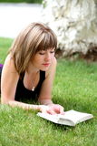 Young happy woman reading a book Stock Images