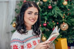 Young happy woman reading book. On christmas Stock Image