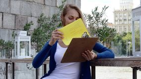 Young happy woman reading menu in street cafe stock video