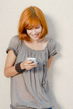 Young happy woman reading message on mobile phone Stock Photo