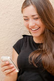 Young happy woman reading message on mobile phone Royalty Free Stock Photos