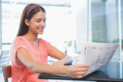 Young happy woman reading the newspaper Royalty Free Stock Photos