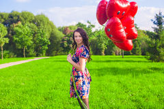 Young happy woman with red balloons walking in the park Stock Photos