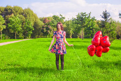 Young happy woman with red balloons walking in the park Royalty Free Stock Images