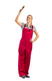 Young happy woman in red jumpsuit with paint brush stock photography