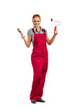 Young happy woman in red jumpsuit with painting tools stock photography