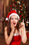 Young happy woman in red santa hat and red dress sitting near ne Stock Images