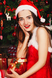 Young happy woman in red santa hat and red dress sitting near ne Royalty Free Stock Image