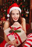 Young happy woman in red santa hat and red dress sitting near ne Royalty Free Stock Photography