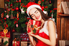 Young happy woman in red santa hat and red dress sitting near ne Royalty Free Stock Photo