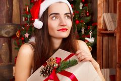 Young happy woman in red santa hat and red dress sitting near ne Royalty Free Stock Photos