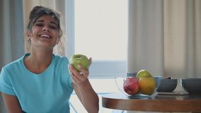 Young happy woman refreshing with cup of coffee, snacks and fresh fruit at the kitchen table in the early morning. stock footage