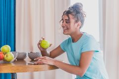Young Happy Woman Refreshing with Cup of Coffee, Snacks and Fresh Fruit at the Kitchen Table in the Early Morning. royalty free stock images