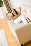 Young happy woman relax lying down on sofa Stock Photo