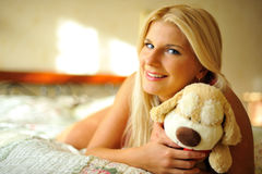 Young happy woman relaxing on a bed Stock Photography