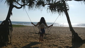 Young happy woman relaxing at swing at tropical ocean beach. Beautiful girl sitting on swing and enjoying summer. Vacation or holiday. Female having fun at sea stock video