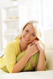 Young and happy woman resting on sofa at home Royalty Free Stock Image