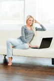 Young and happy woman resting on sofa at home Stock Photos