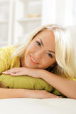 Young and happy woman resting on sofa at home and drinking coffee Stock Photography