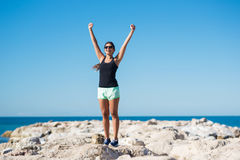 Young happy woman rising hands in victory gesture. Full portrait of young happy woman rising hands in victory gesture Royalty Free Stock Photography