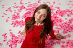 Young happy woman in rose petals Stock Images