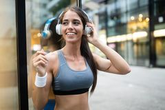 Young happy woman runner jogging in city outdoor stock photography
