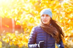 Young happy woman running in autumn park. Against yellow foliage tree Stock Image