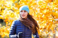 Young happy woman running in autumn park. Against yellow foliage tree Royalty Free Stock Image