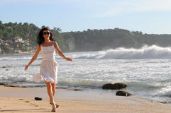 Young happy woman running on a beach. Young woman running on a beach royalty free stock photos