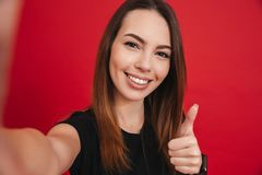 Young happy woman 20s with long brown hair smiling and taking se. Lfie with gesturing thumb up isolated over red background Royalty Free Stock Photo