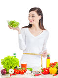 Young happy woman with salad measuring her waistline. Royalty Free Stock Photos