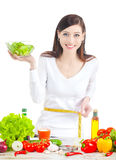 Young happy woman with salad measuring her waistline. Royalty Free Stock Photo