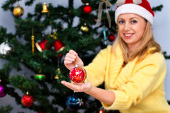 Young happy woman in santa hat is holding a christmas ball Royalty Free Stock Images