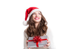 Young happy woman in santa hat looking sideways showing Christmas present. Royalty Free Stock Photography