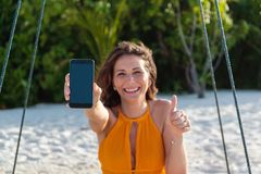 Young happy woman seated on a swing showing a vertical phone screen. White sand and jungle as background stock photo