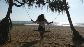 Young happy woman in shirt relaxing at swing at tropical ocean beach. Beautiful girl sitting on swing and enjoying. Summer vacation or holiday. Female having stock video footage