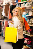 Young happy woman with shopping bags leaving a sho Royalty Free Stock Photo