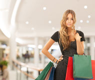 Young happy woman with shopping bags in mall Stock Photo