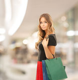 Young happy woman with shopping bags in mall Stock Images