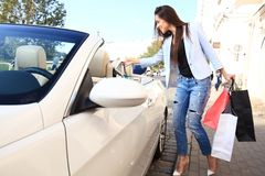 Young happy woman with shopping bags near the car outdoors. Royalty Free Stock Images