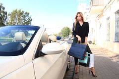 Young happy woman with shopping bags near the car outdoors. Royalty Free Stock Photos