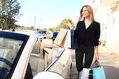 Young happy woman with shopping bags near the car outdoors. Royalty Free Stock Photo