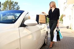 Young happy woman with shopping bags near the car outdoors. Stock Image