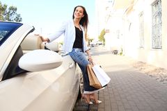 Young happy woman with shopping bags near the car outdoors. stock photography