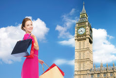 Young happy woman with shopping bags over big ben Royalty Free Stock Photos