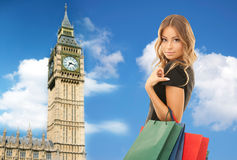 Young happy woman with shopping bags over big ben Royalty Free Stock Images