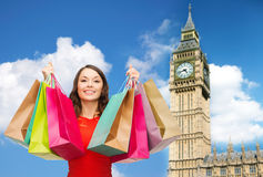 Young happy woman with shopping bags over big ben Royalty Free Stock Image