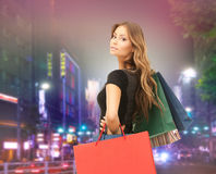 Young happy woman with shopping bags over city Royalty Free Stock Images