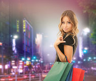 Young happy woman with shopping bags over city Royalty Free Stock Photos