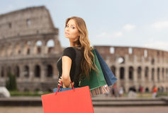 Young happy woman with shopping bags over coliseum Stock Photography
